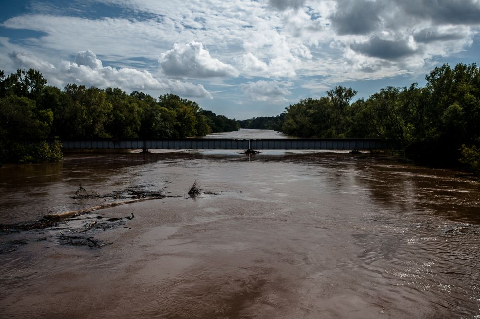 Trees and other debris flow down the flooded Cape Fear River in Fayetteville, North Carolina, on Monday