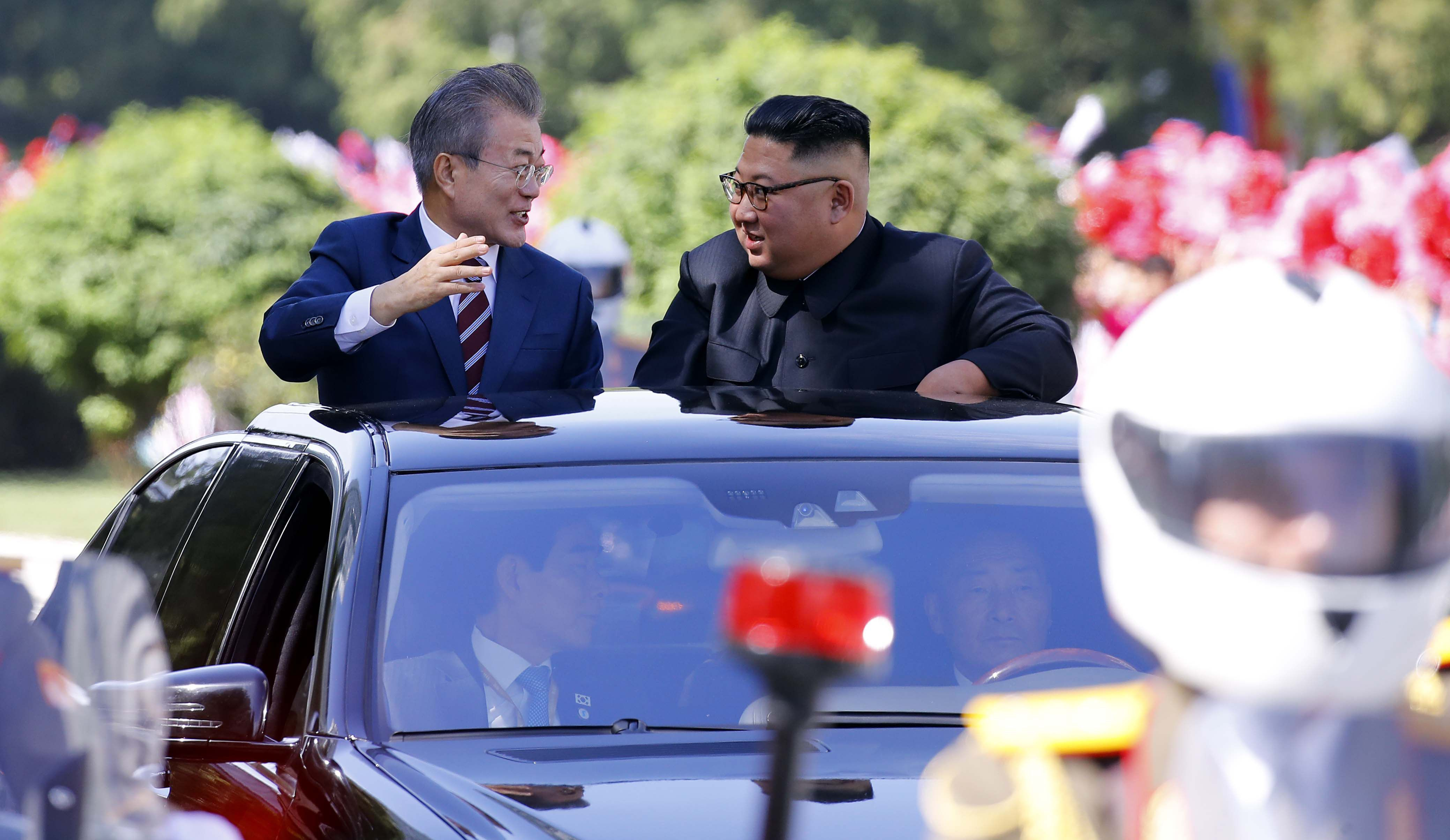 South Korean President Moon Jae-in, left, and North Korean leader Kim Jong-un ride in a car parade in...