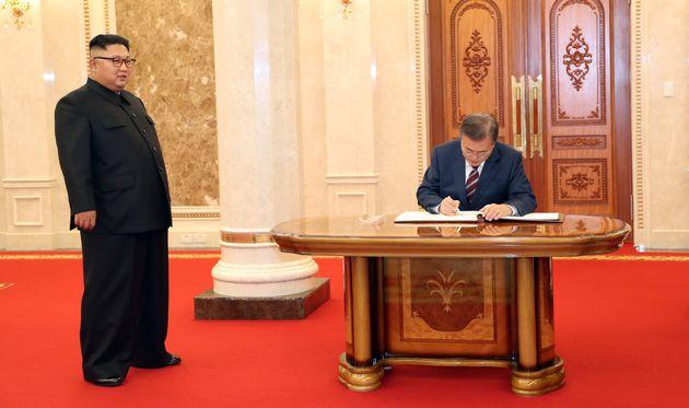 문재인 대통령이 18일 오후 평양 조선노동당 중앙위원회 본부 청사에서 김정은 국무위원장이 지켜보는 가운데 방명록에 서명하고 있다.