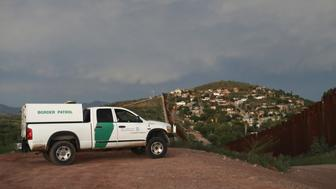 NOGALES, AZ - JULY 22:  A U.S. Border Patrol agent watches over the U.S.-Mexico border at dusk on July 22, 2018 in Nogales, Arizona. President Trump has proposed replacing the fence with a wall. At left is seen a security camera mounted above the Mexican side of the border.  (Photo by John Moore/Getty Images)