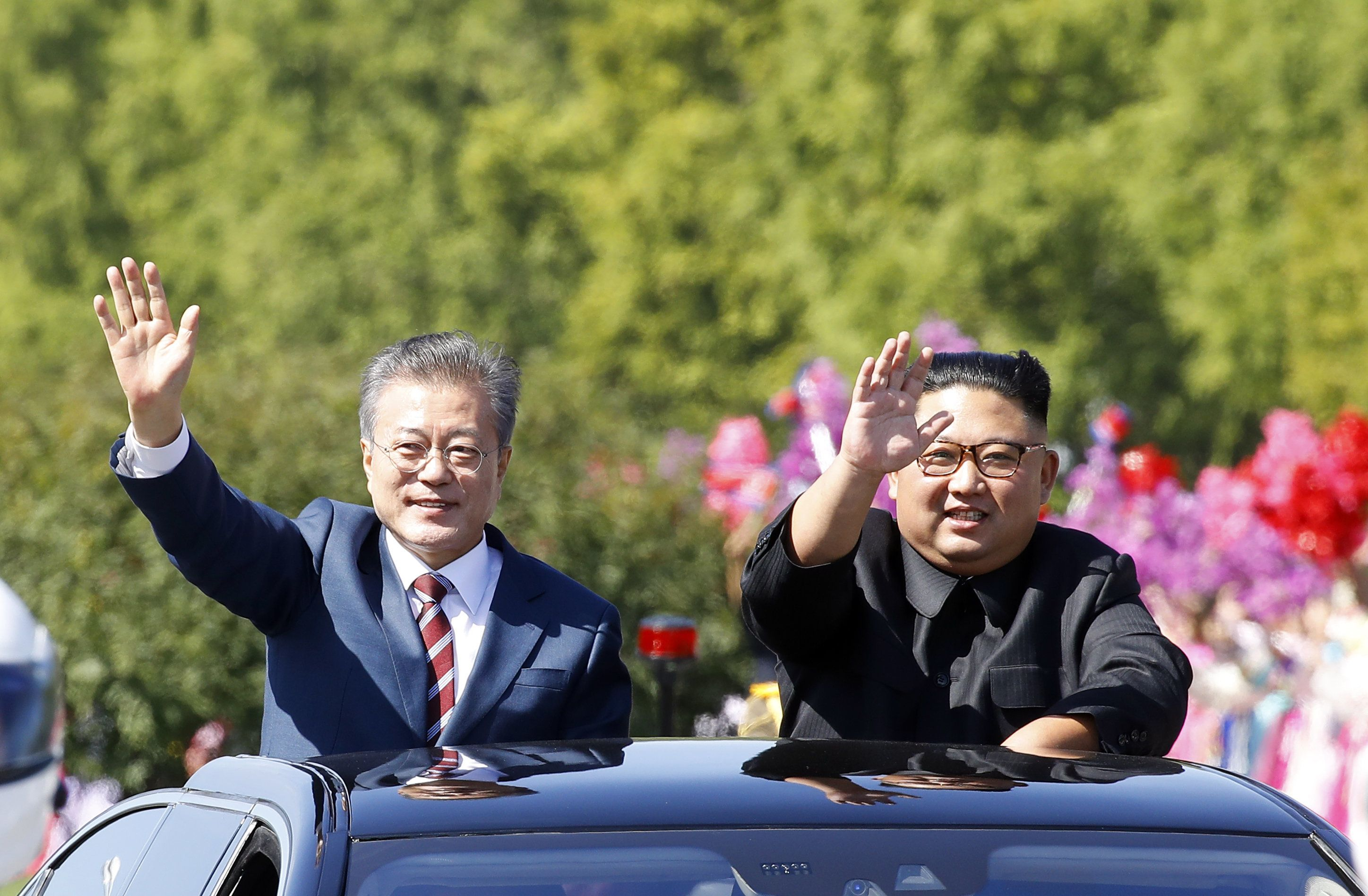 PYONGYANG, NORTH KOREA - SEPTEMBER 18: (EDITORIAL USE ONLY, NO COMMERCIAL USE) South Korean President Moon Jae-in (L) and North Korean leader Kim Jong-un (R) ride in a car parade on September 18, 2018 in Pyongyang, North Korea. Kim and Moon meet for the Inter-Korean summit talks after the 1945 division of the peninsula, and will discuss ways to denuclearize the Korean Peninsula. (Photo by Pyeongyang Press Corps/Getty Images)