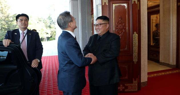 South Korean President Moon Jae-in is greeted by North Korean leader Kim Jong Un as he arrives at the...