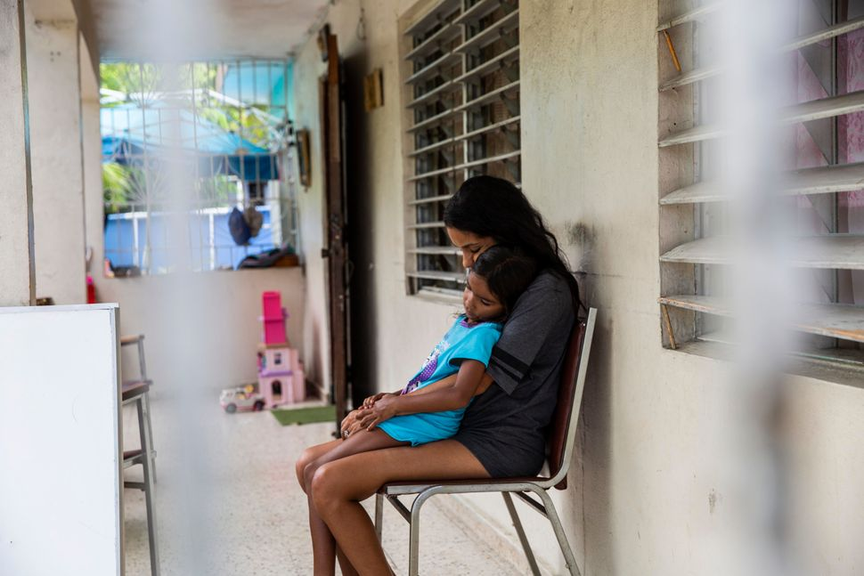 Betsy Rosado Sánchez comforts her youngest daughter, 6-year-old Marina, on their front porch. Marina, like her older s