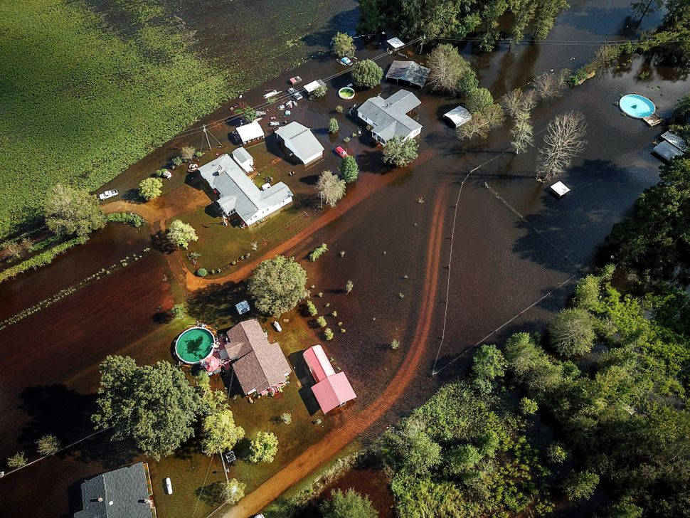 A flooded neighborhood stands next to the Black Swamp River in Lumberton.