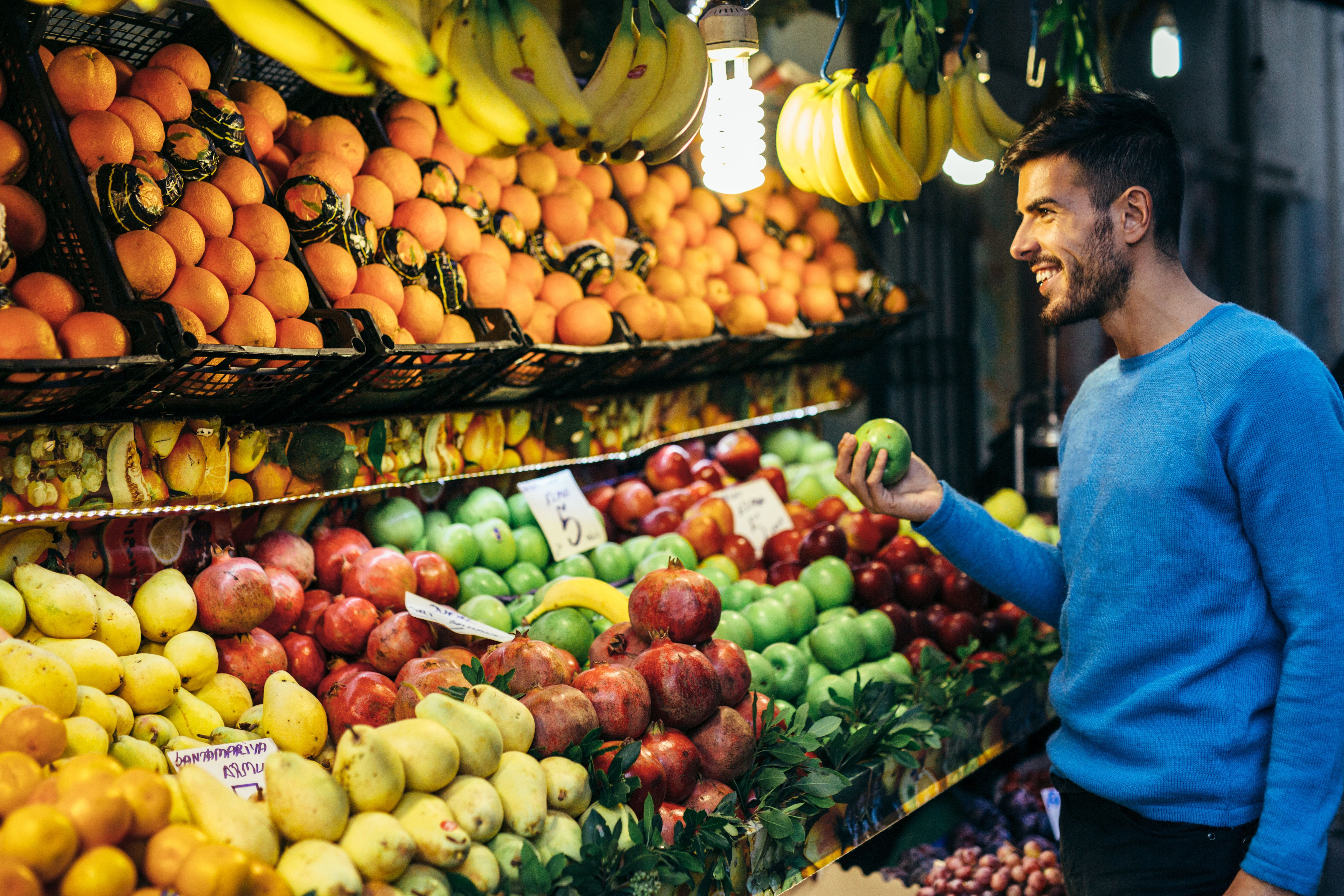 A man shopping some fruits.