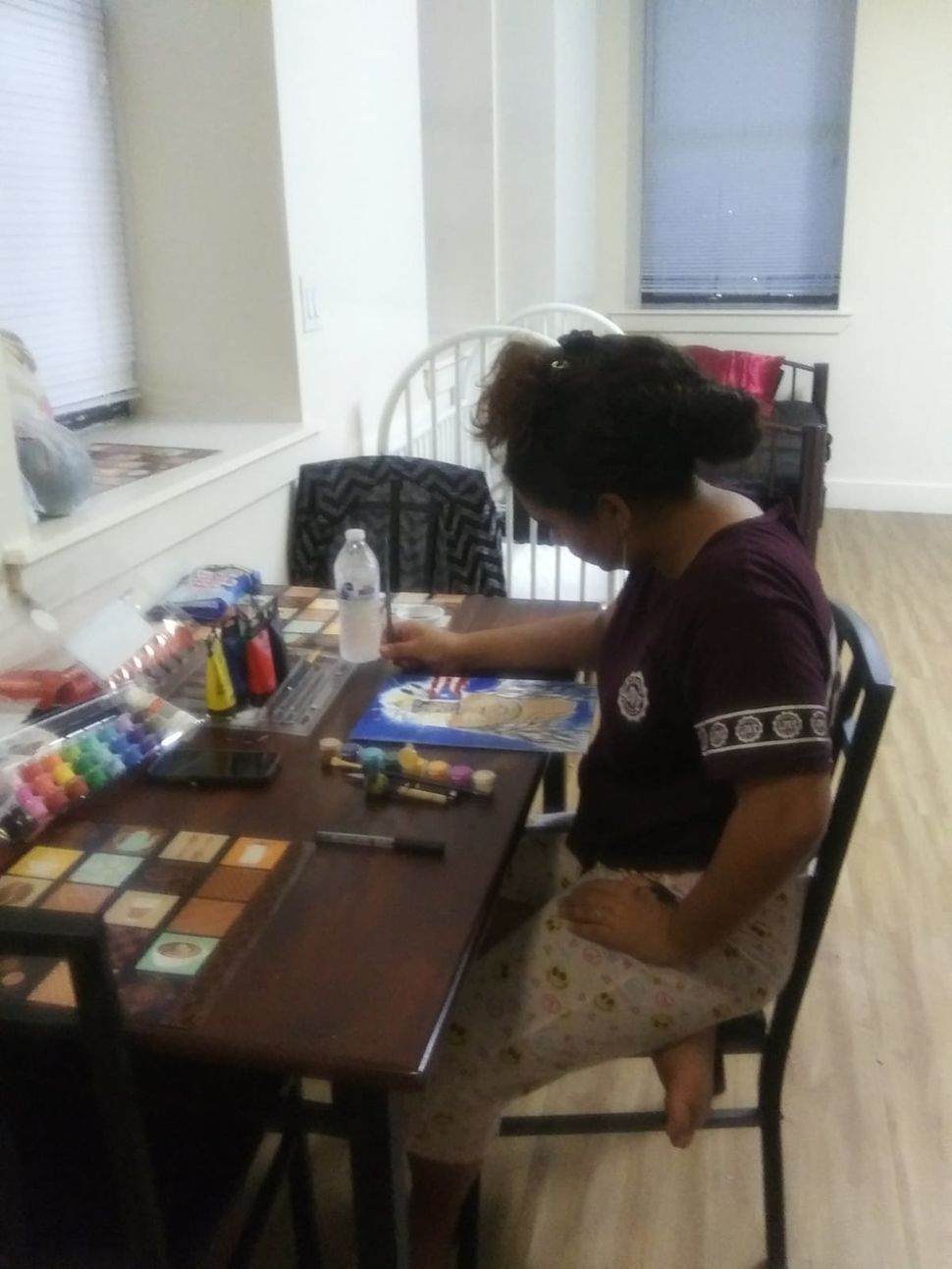 Jennyfer's daughter, 14, painting at the table in their room at the Bronx shelter