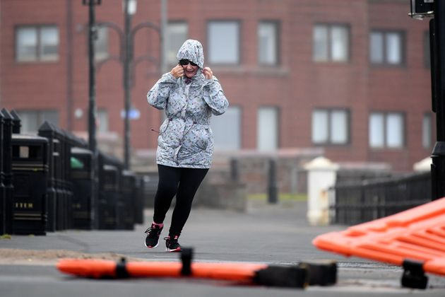 A woman struggles in the wind in Saltcoats,