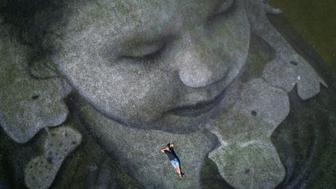 TOPSHOT - This aerial view shows French artist Saype posing inside his giant land art fresco representing a little girl droping an origami boat into Lake Geneva that he painted to support the cause of the NGO SOS Mediterranee, specializes in the rescue of migrants at sea on September 17, 2018 in Geneva. - The giant fresco covering 5,000 square meters was produced with biodegradable paints made from natural pigments. (Photo by Fabrice COFFRINI / AFP) / RESTRICTED TO EDITORIAL USE - MANDATORY MENTION OF THE ARTIST UPON PUBLICATION - TO ILLUSTRATE THE EVENT AS SPECIFIED IN THE CAPTION        (Photo credit should read FABRICE COFFRINI/AFP/Getty Images)