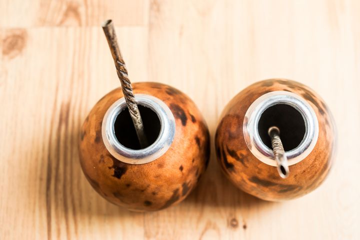 Traditional vessels used to drink yerba mate included metal or wooden straws.