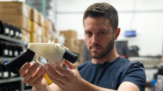 TOPSHOT - Cody Wilson, owner of Defense Distributed company, holds a 3D printed gun, called the 'Liberator', in his factory in Austin, Texas on August 1, 2018. - The US 'crypto-anarchist' who caused panic this week by publishing online blueprints for 3D-printed firearms said Wednesday that whatever the outcome of a legal battle, he has already succeeded in his political goal of spreading the designs far and wide. A federal court judge blocked Texan Cody Wilson's website on Tuesday, July 31, 2018, by issuing a temporary injunction. (Photo by Kelly WEST / AFP)        (Photo credit should read KELLY WEST/AFP/Getty Images)