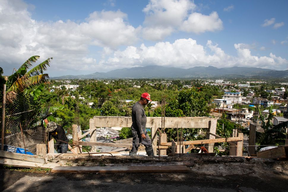 Workers rebuild a home in Villa Hugo 2 nearly a year after the storm.