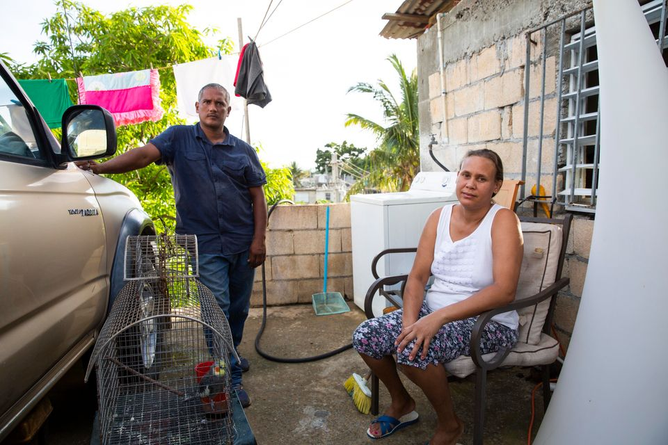 In August, Guerrero Herrera and his wife, Daysi Lantigua, sit on the front porch of their new cement...