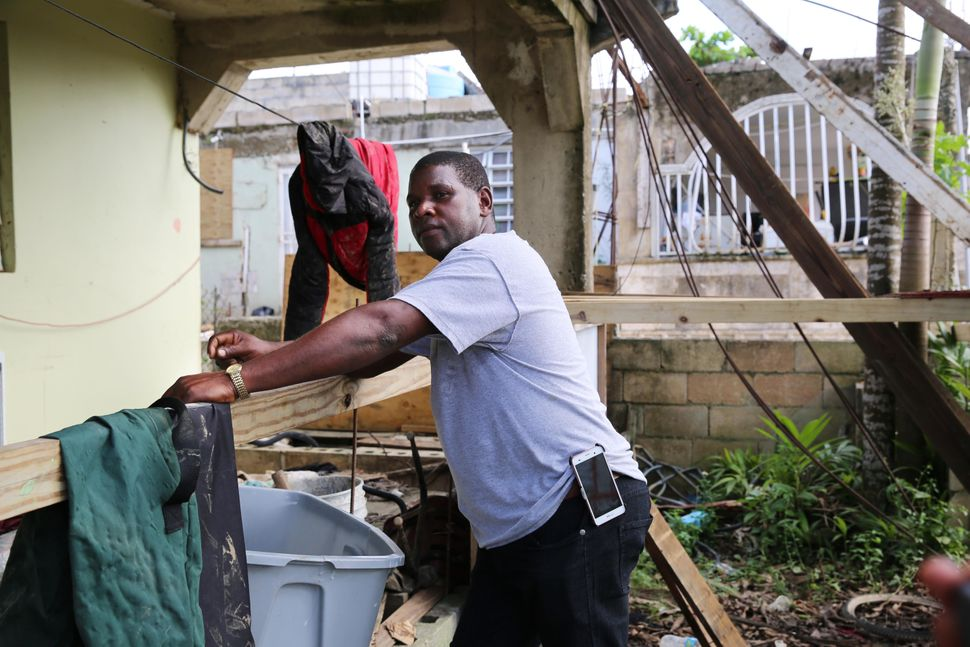 After sorting through his damaged belongings, Juan Medina-Dishmey rests on his front porch three weeks after the storm.