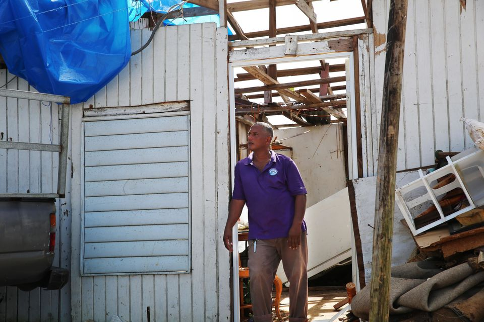Three weeks after the storm, Danny Guerrero Herrera stands at the door of his home, which was largely...
