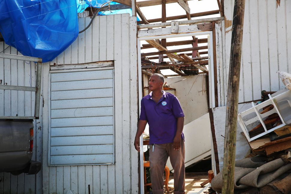 Three weeks after the storm, Danny Guerrero Herrera stands at the door of his home, which was largely destroyed by Hurricane