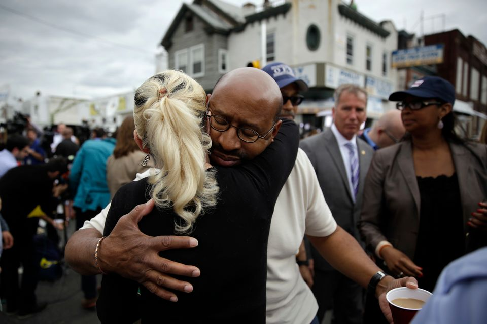 Philadelphia Mayor Michael Nutter, center right, hugs Lori Dee Patterson, a nearby resident, after she handed him a cup of co