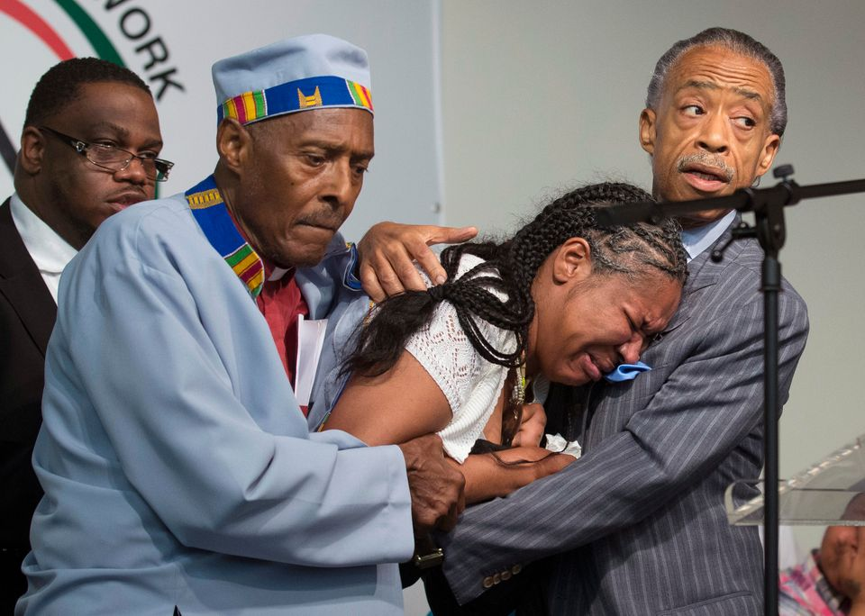 FILE - In this July 19, 2014, file photo, Esaw Garner, center, wife of Eric Garner, breaks down in the arms of Rev. Herbert D