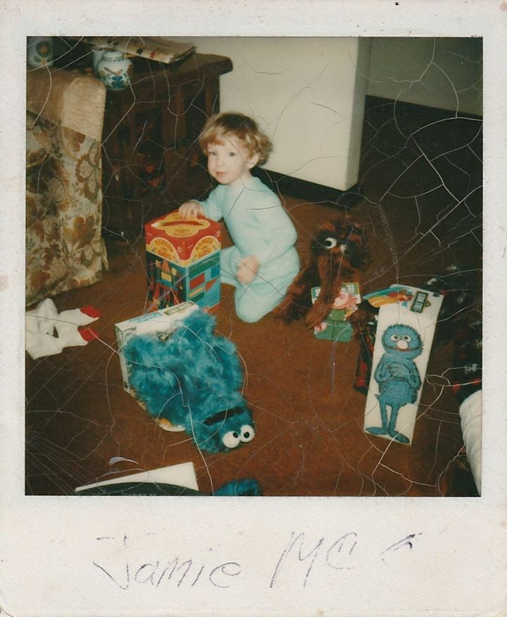 "Jamie McGonnigal as a child at Christmas with his ""Sesame Street"" toys."