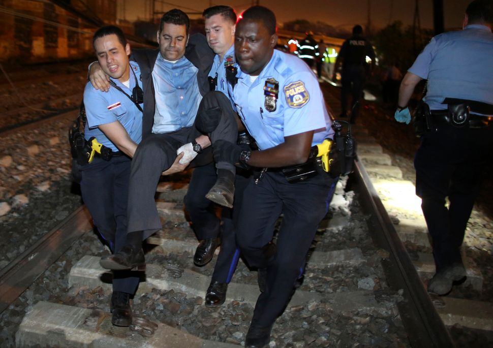 Emergency personnel help a passenger at the scene of a train wreck, Tuesday, May 12, 2015, in Philadelphia.