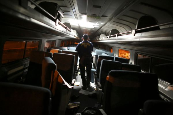 A crime scene investigator looks inside a train car after a train wreck, Tuesday, May 12, 2015, in Philadelphia.