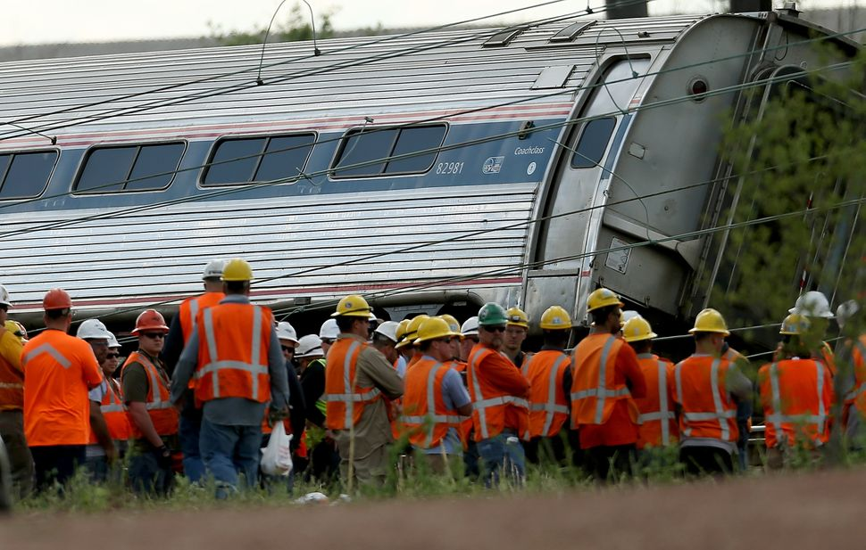 Investigators and first responders work near the wreckage of an Amtrak passenger train carrying more than 200 passengers from