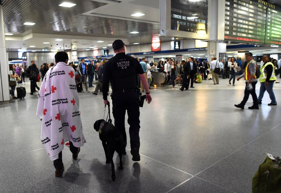 Passengers injured in an Amtrak train derailment who were bused from to New York from Philadelphia, walk through Penn Station