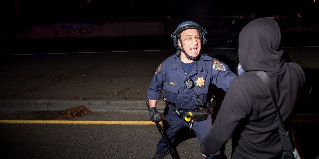 A police officer tries unsuccessfully to keep a protester from blocking Interstate 580 in Oakland, Calif on Monday, Nov. 24,