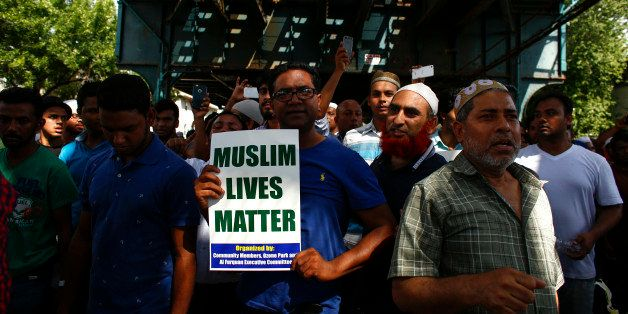 Community members march in protest in the streets after funeral prayers were given for Imam Maulama Akonjee and friend Thara