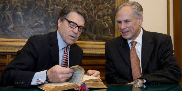 Texas Gov. Rick Perry, left, points out a passage in the Governor Neff Bible that he marked for Texas Gov.-elect Greg Abbott,