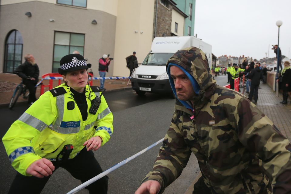 ABERYSTWYTH, WALES - OCTOBER 08:  A police officer tries to prevent a member of the public from getting at a prison van belie
