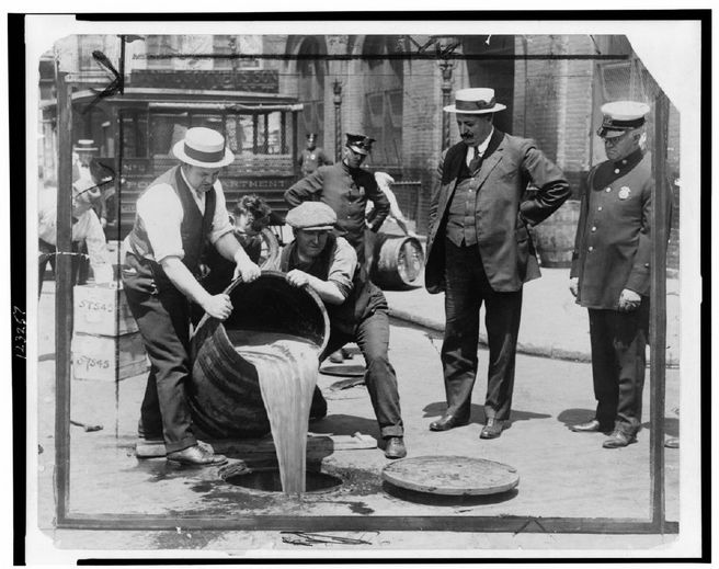 New York City Deputy Police Commissioner John A. Leach, back right, watches agents pour liquor into a sewer following a raid