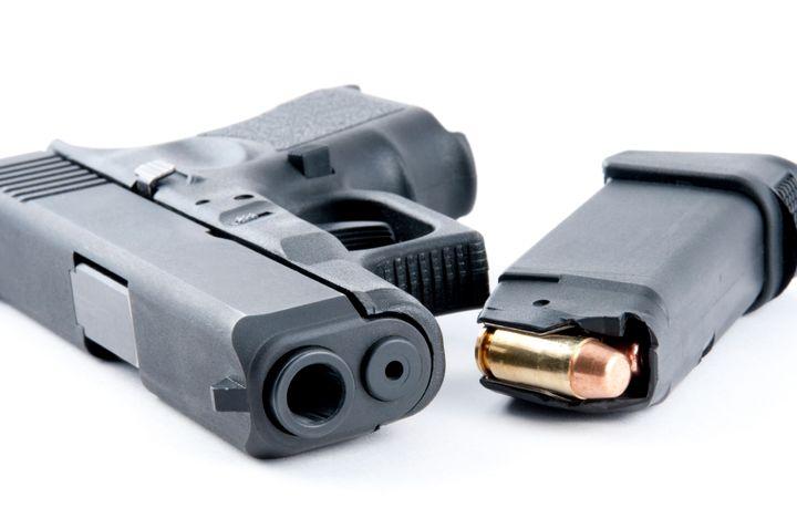 Large caliber handgun with 40 caliber ammunition lying next to a loaded clip.