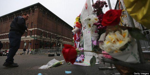 BOSTON, MA - APRIL 23:  A man views a makeshift memorial at a barricade blocking a still closed section of Boylston Street ne