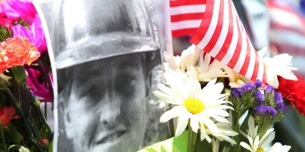 A fallen firefighter's picture is part of a memorial outside of the Granite Mountain Hotshot fire station in Prescott, Arizon