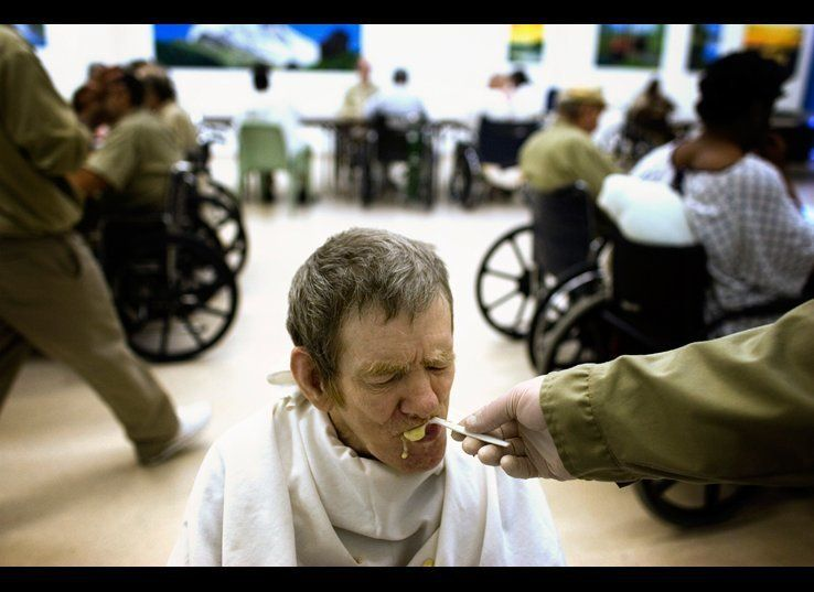 Charlie Coffey, 65, is fed his lunch. He has been in prison for over 30 years.