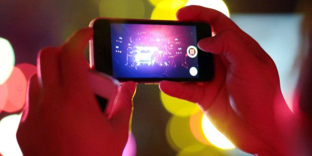Man used mobile phone camera take pictures in the Concert party