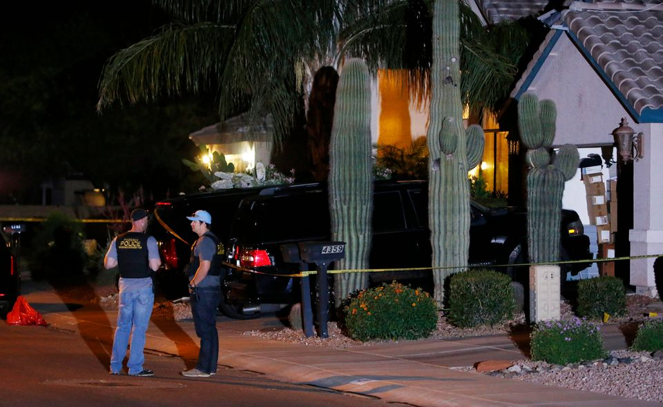 Phoenix Police Department officers stand out in front of a home where authorities say five people were killed inside after a