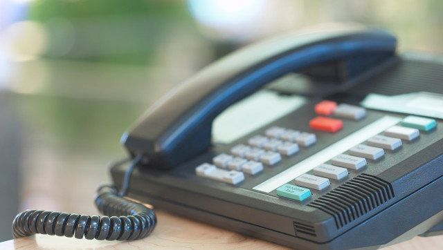 Business telephone with extensions on desk in office
