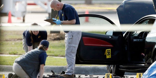 FBI crime scene investigators document the area around two deceased gunmen and their vehicle outside the Curtis Culwell Cente