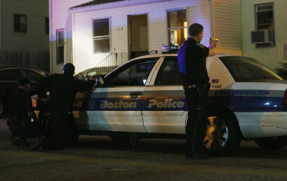 A police officer with gun drawn searches for a suspect on April 19, 2013 in Watertown, Massachusetts. Earlier, a Massachusett