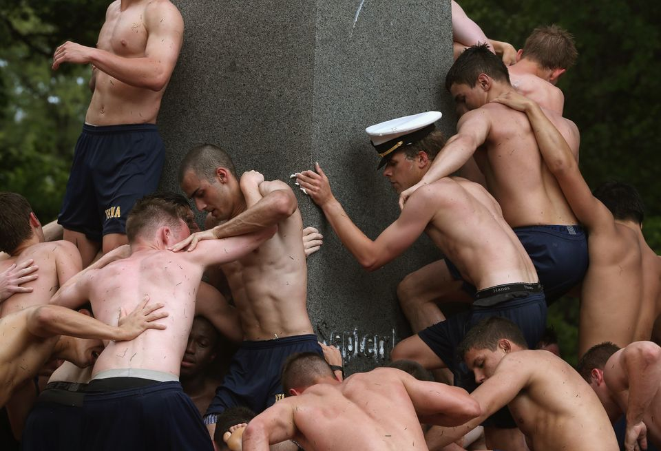 ANNAPOLIS, MD - MAY 19:  Annapolis Naval Academy freshmen make a human wall to climb the lard covered Herndon Monument on May