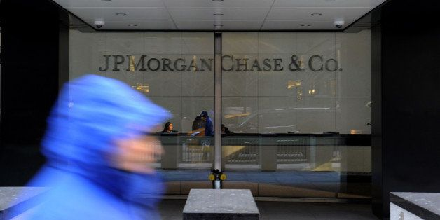 A pedestrian passes by JPMorgan Chase & Co. offices in New York, U.S., on Tuesday, Jan. 7, 2014. JPMorgan Chase & Co. agreed