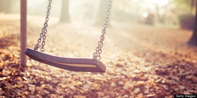 Moving playground swing in last sun light in autumn.