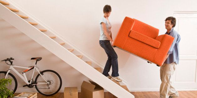 Couple carrying armchair up stairs