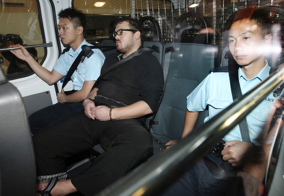 Rurik George Caton Jutting, center, is escorted by police officers in an police van before appearing in a court in Hong Kong