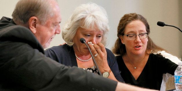 Debra Milke cries as she is attended to by by Attorneys Lori Voepel, right, and Michael Kimerer during a news conference, Tue