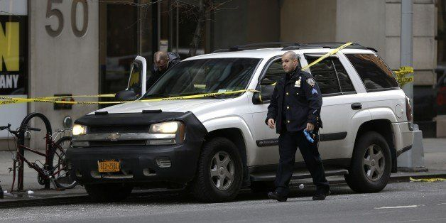New York City Police officers work the scene of a shooting at a Home Depot, Sunday, Jan. 25, 2015, in New York. Police said a