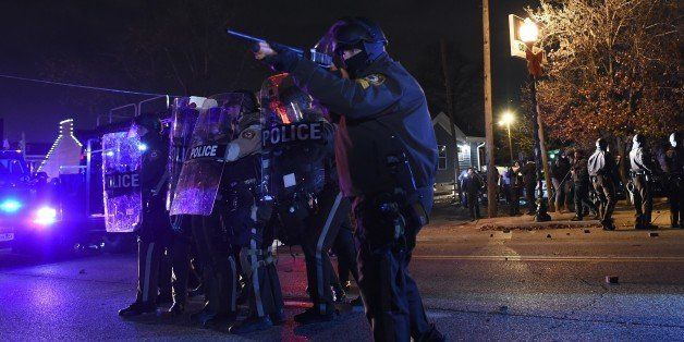 Police points his rifle at demonstrators after a grand jury decided a white policeman will not face charges for killing a bla
