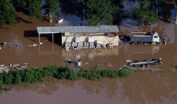 In this aerial photo, a building and dump truck are surrounded by floodwaters near the Brazos River Saturday, May 30, 2015, i