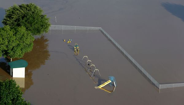 In this aerial photo, a school playground is covered by floodwaters near the Brazos River Saturday, May 30, 2015, in Rosenber